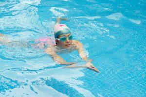 Girl swimming breaststroke in the pool